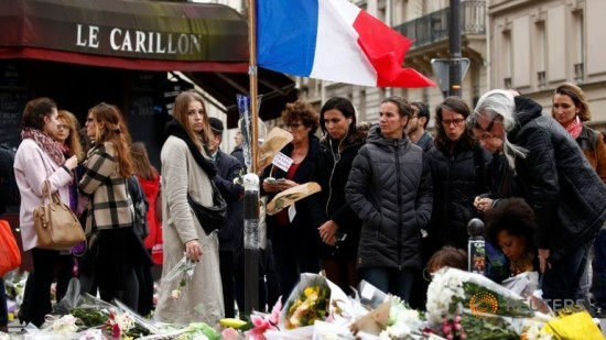"People mourn outside ""Le Petit Cambodge"" resturants as they pay tribute to the victims of the series of deadly attacks last Friday"