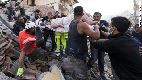Rescue Teams pull injured woman from a collapse building in Amatrice after massive earth quake. Photo Credit: CNN