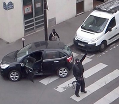 Gunmen gesture as they return to their car after the attack outside of the offices of french satirical weekly newspaper office