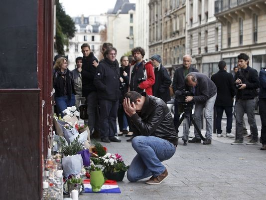 A man holds his head in his hands while placing flowers a memorial in Paris.